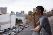 Молода людина, пити каву на балконі вдома — стокове фото