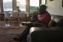 Hijo de padre y niño tocando la guitarra en la sala de estar en casa - foto de stock