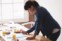 Female executive checking a documents in the creative office — Stock Photo