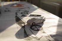 Модель автомобіля на діаграмі та ескізи на столі в офісі. — стокове фото