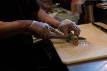 Koch-slicing-Sushi Rollen auf einem Schneidebrett — Stockfoto