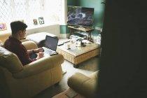Человек, используя ноутбук в кресло в гостиной дома — стоковое фото