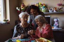 Zwei ältere Frauen machen künstliche Blume mit Hausmeister im Pflegeheim — Stockfoto