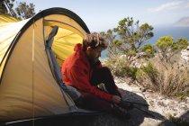 Wanderer im Zelt seine Schnürsenkel zu binden, an einem sonnigen Tag sitzen — Stockfoto