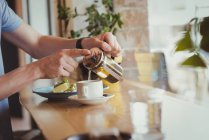 Mid section of man pouring coffee in cup at table — Stock Photo