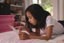 Girl using digital tablet in bedroom at home — Stock Photo