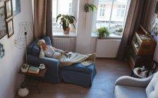 Vista di alto angolo della donna senior che si distende sul sofà con uno smart phone che ascolta la musica a casa — Foto stock