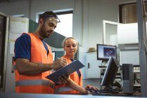Two worker discussing over clipboard in factory — Stock Photo
