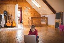 Lindo niño usando el ordenador portátil en el suelo de madera en casa - foto de stock