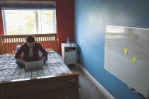 Hombre joven que trabaja con el ordenador portátil en la cama en casa . - foto de stock