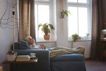 Задумчивая пожилая женщина отдыхает на диване в гостиной на дому — стоковое фото