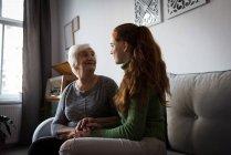 Grand-mère et petite-fille interagissant dans le salon à la maison — Photo de stock