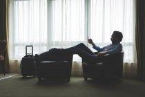 Homme d'affaires à l'aide de téléphone portable dans la chambre d'hôtel — Photo de stock