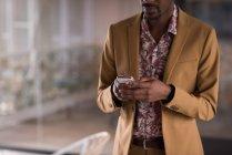 Mittelteil des Geschäftsmannes mit Handy im Büro — Stockfoto