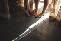 Close-up of female feet standing on wooden floor near window at home. — Stock Photo
