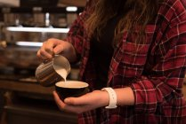 Mid section of female barista preparing coffee at counter in cafe — Stock Photo