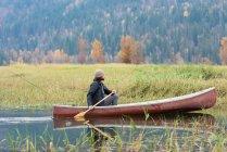 Homme aviron canot dans la rivière près des prairies — Photo de stock