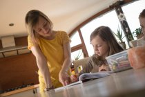 Mother helping children with homework in kitchen at home — Stock Photo