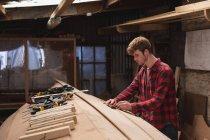 Jeune mâle charpentier travaillant dans l'atelier — Photo de stock