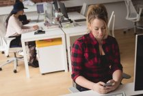Женщины Исполнительный, с помощью мобильного телефона в отделе творческой — стоковое фото