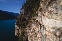 Grimpeur déterminé grimper la falaise près de la mer — Photo de stock