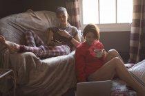 Гомосексуальная пара, пользующаяся мобильным телефоном и ноутбуком, пьет кофе дома . — стоковое фото