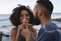 Пара, имеющие мороженое возле моря в Солнечный день — стоковое фото