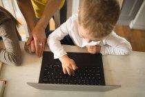 Крупным планом мать сына преподавание с помощью ноутбуков на дому — стоковое фото