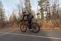Байкер верхом на горном велосипеде по дороге в солнечный день — стоковое фото