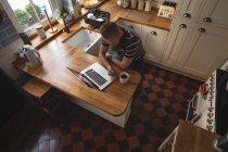 Uomo seduto sulla sedia con il cellulare in cucina a casa — Foto stock