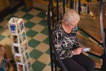 Старшие женщины, используя мобильный телефон в магазине антикварные книги — стоковое фото