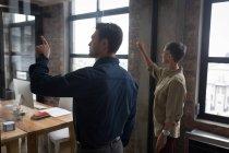 Колегами по бізнесу за допомогою невидимий екраном в офісі. — стокове фото