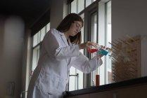 Teenager-Mädchen experimentiert mit chemischer Lösung im Labor — Stockfoto