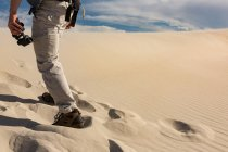 Low section of male hiker with binoculars walking on sand — Stock Photo