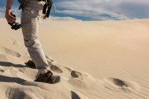 Bassa sezione di escursionista maschio con binocolo che cammina sulla sabbia — Foto stock