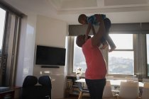 Father lifting son while playing in living room at home. — Stock Photo