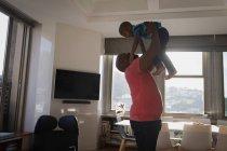 Padre sollevamento figlio mentre gioca in soggiorno a casa . — Foto stock