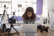 Фотограф с помощью ноутбука на стойке в фото студии — стоковое фото