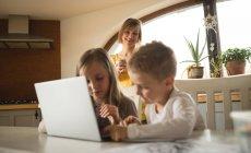 Mutter, die gerade Kinder mit Laptop in der Küche zu Hause — Stockfoto