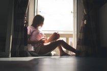 Женщина сидит у окна и пьет кофе дома . — стоковое фото