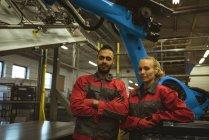 Портрет чоловічих і жіночих працівник стояли разом із зброї, перейшли на заводі — стокове фото