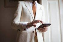 Partie médiane du marié utilisant son téléphone portable à la maison — Photo de stock