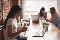 Executive mit Handy während Kollegen diskutieren im Hintergrund im Büro — Stockfoto