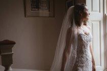 Мрійливий нареченої дивиться з вікна на дому — стокове фото