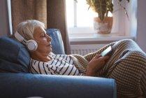 Пожилая женщина слушала музыку по телефону, сидя на диване в гостиной дома — стоковое фото