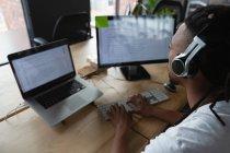Ejecutiva masculina con auriculares trabajando en el escritorio en la oficina . - foto de stock