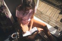 Femme écrivant dans un journal intime près de la fenêtre à la lumière du soleil à la maison . — Photo de stock
