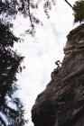 Vista ad angolo basso dell'arrampicatore arrampicatore sulla scogliera rocciosa — Foto stock