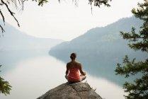 Стройная женщина, сидящая в позе медитирующей на краю скалы на рассвете — стоковое фото