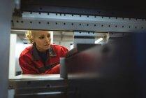 Женщина-работница проверяет машину на заводе — стоковое фото